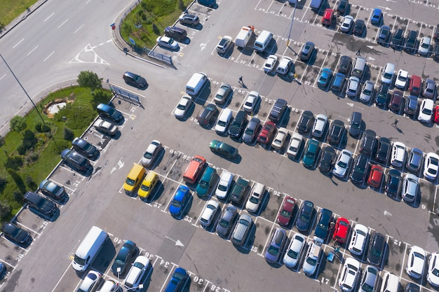 Plenty of cars in the packed parking lot in straight rows from a bird's-eye view
