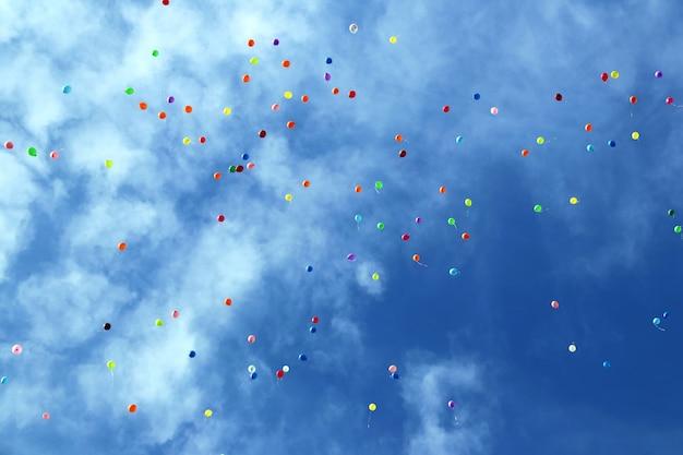 青い空にたくさんの色とりどりの風船