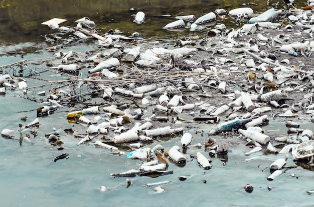 하천 오염의 바닥에 많은 플라스틱 및 유리 병