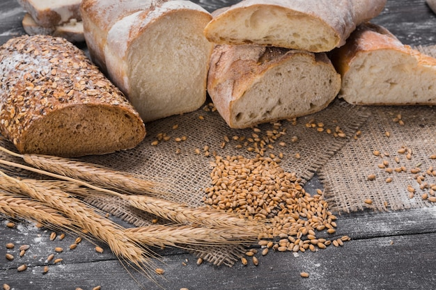 Plenty of sliced bread. bakery and grocery concept. fresh, healthy whole grain sliced sorts of rye and white loaves, sprinkled flour on sackcloth and rustic wood table, food closeup.
