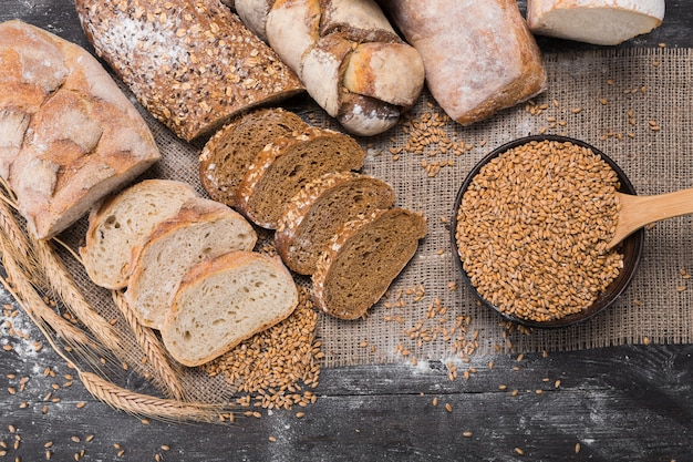 Plenty of sliced bread. bakery and grocery concept. fresh, healthy whole grain sliced sorts of rye and white loaves, sprinkled flour on sackcloth and rustic wood table, food top view