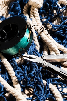 Plier and fishing hooks on blue fishing net