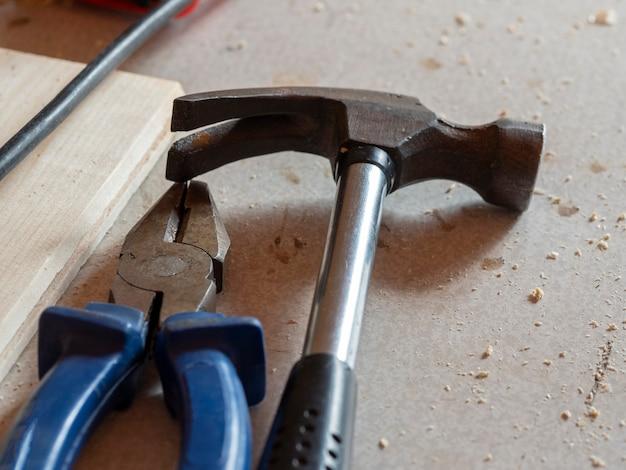На столе - плоскогубцы и молоток. крупный план, жесткие тени, выборочный фокус. инструменты для работы