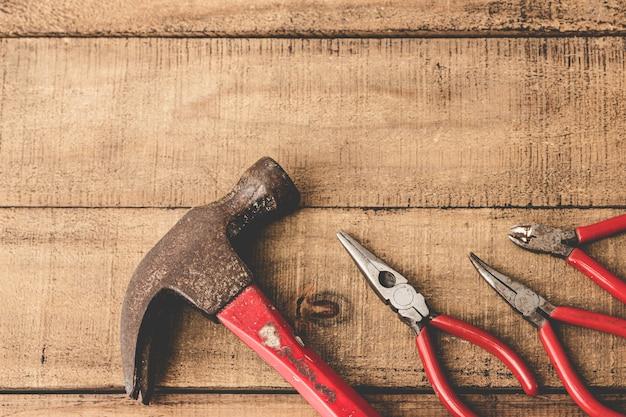 Плоскогубцы и молоток на деревянный стол. копировать пространство