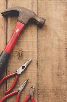 Плоскогубцы и молоток на деревянный стол.