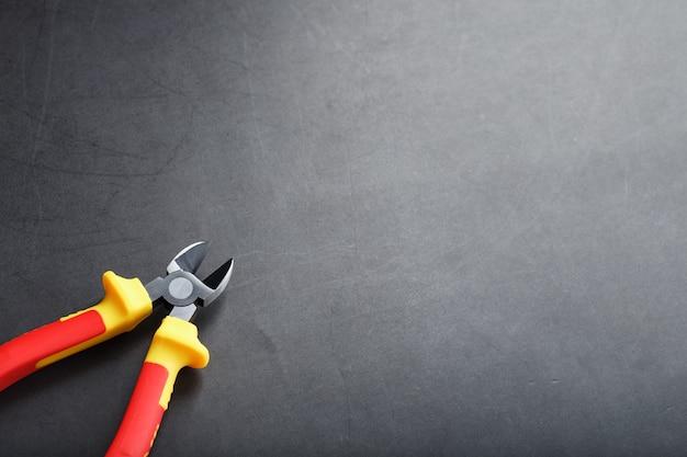 ペンチは、黒い背景に赤いハンドルが付いた切削工具です