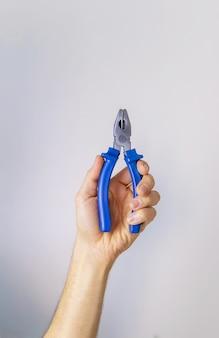 男性の分離株の手で修理するためのペンチ。セレクティブフォーカス。