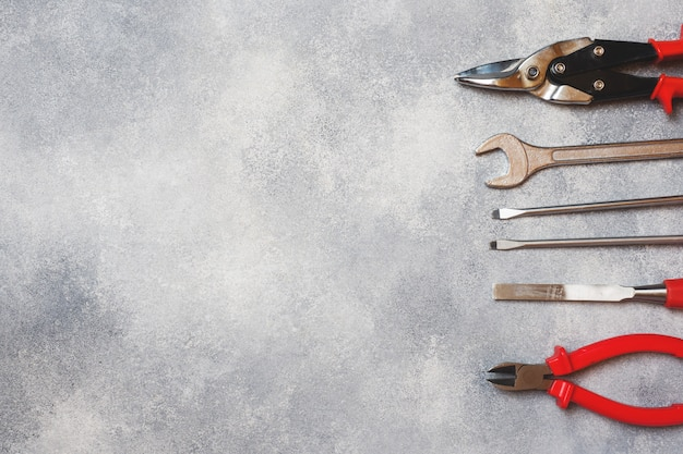 Pliers, screwdrivers and wrench combination on grey concrete background with copy space.