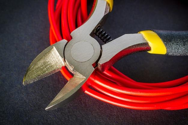 Плоскогубцы инструмент и красные провода для электрика крупным планом