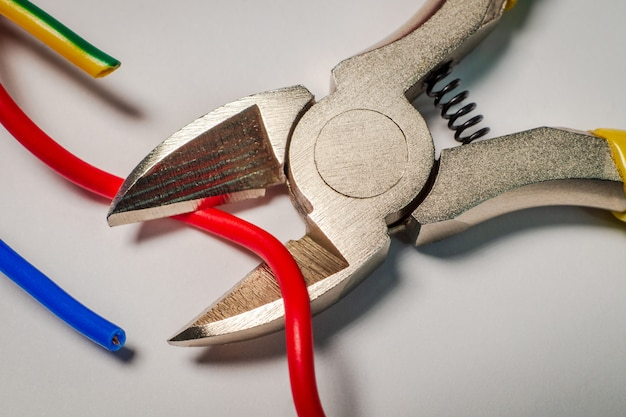 Pliers tool cutting electric wire closeup