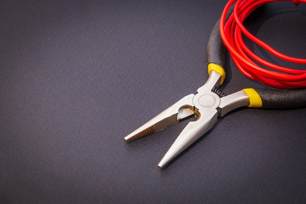 Pliers tool and red wires for electrician