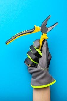 ペンチ。青いモノクロの背景に電気技師の手に黄色と黒のペンチ。修理およびインストールツール。建設トピックのデザインと印刷のためのバナー。