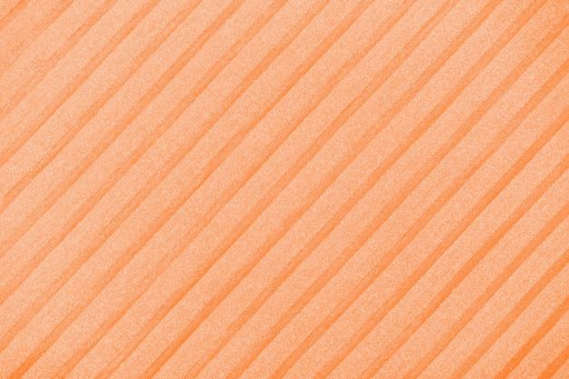 Plisse background toned in orange peel. geometric cloth lines. fabric, textile close up.