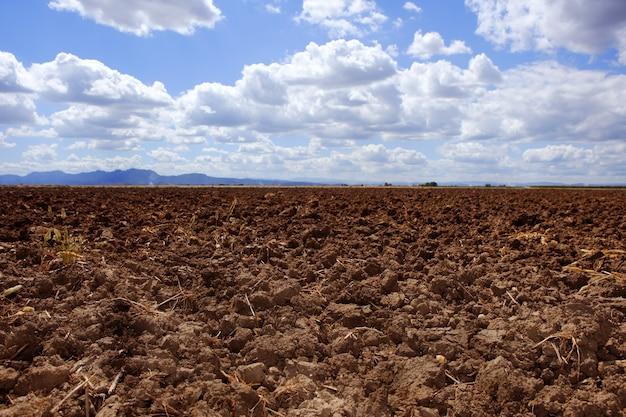 Плуг вспаханный бурой глиняной поля голубое небо горизонт