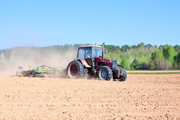 耕作農業の間にトラクターを耕すことはプラウとフィールドで働きます