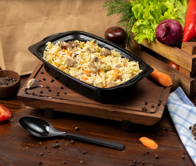 Plov, rice garnish with vegetables, carrots, chestnuts and beef pieces takeaway