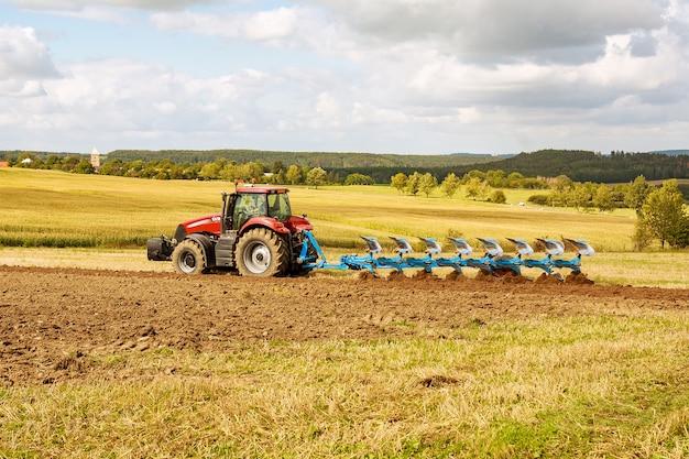 땅을 쟁기질하십시오. 파종을 위해 쟁기와 땅을 준비하는 빨간 트랙터 농부