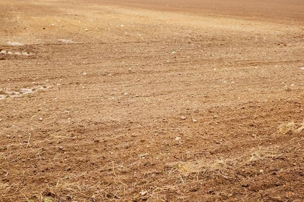 Вспаханное поле со следами от шин сбоку