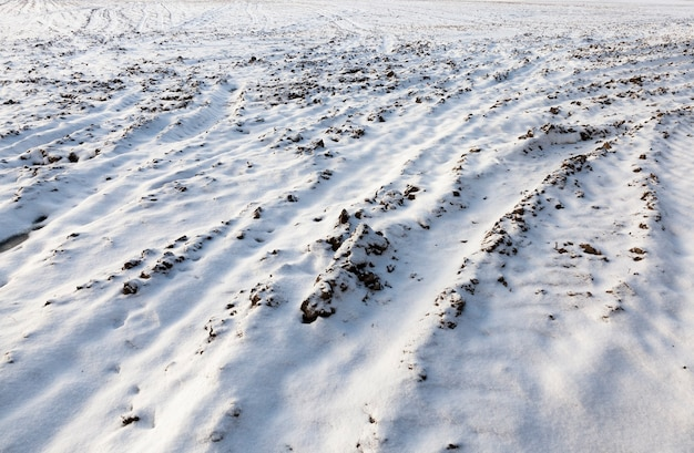 Вспаханная почва под белым снегом, на поверхности видны следы транспортируемого транспорта, крупный план в зимний холод и снежные метели
