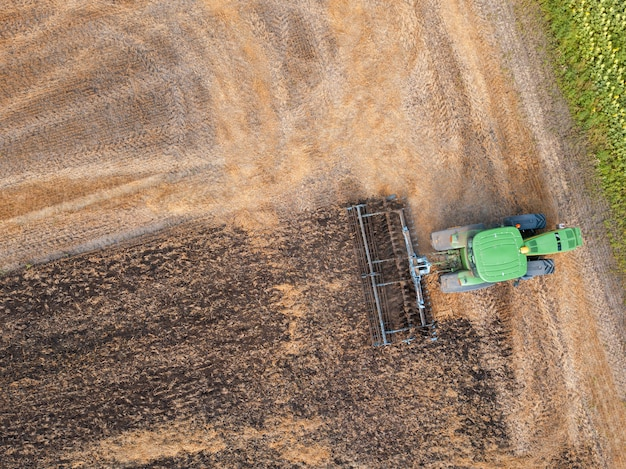 Plowing the ground after harvesting on the field in the autumn time. aerial view from the drone of the field after harvest