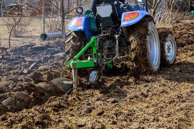 밭을 갈고 있습니다. 농업용 부착물이 달린 작은 트랙터가 땅을 경작합니다.