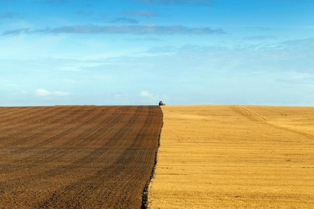 小麦を収穫した後、トラクターの土を耕す