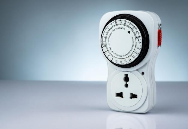 プラグインタイマーの機械式24時間。屋内のホームツール。白い背景に分離されたプラグインタイマーソケットセット。機械式コンセントタイマー。ホームセキュリティの供給。スマートホームツール。機械式タイマースイッチ。