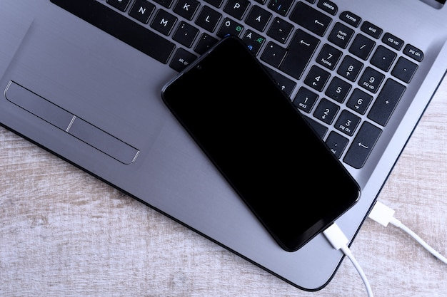 Подключите usb-шнур, зарядное устройство, зарядку, зарядку и передачу данных мобильного телефона, смартфона с ноутбуком на деревянный пол, вид сверху стола