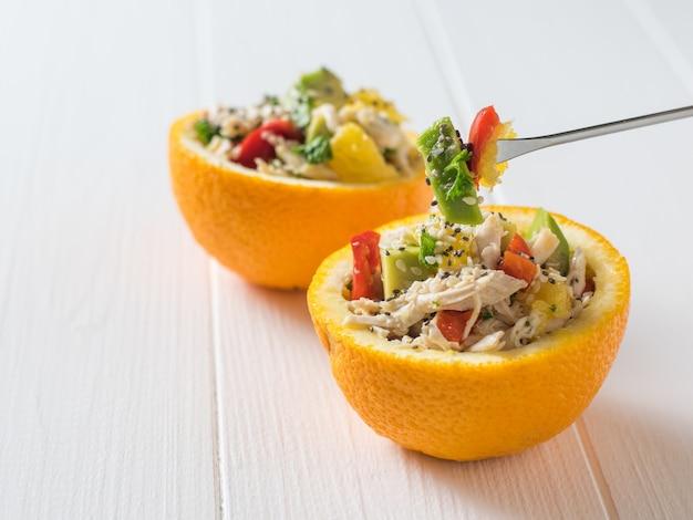 Положите кусочки салата на половинки апельсина. диетическое питание из тропических фруктов и курицы.