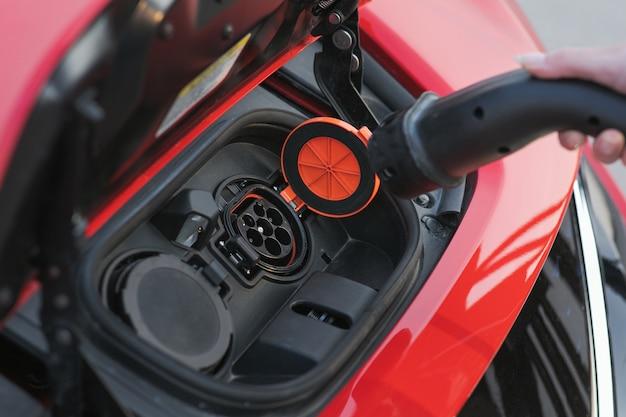 Вставляет зарядное устройство в гнездо ее современного нового красного электромобиля. женщина подключает электромобиль для зарядки аккумулятора на парковке Premium Фотографии