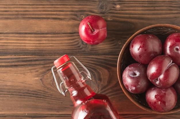 木製のテーブルに梅アルコールとベリー。ベリープラムから作られた自家製のアルコール飲料。フラットレイ上からの眺め。