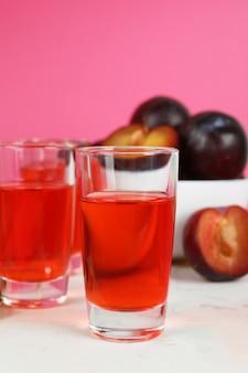 분홍색 배경에 매실 브랜디 샷과 재료