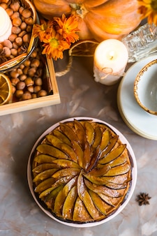 Сливовый торт украшенный нарезанной сливой среди осеннего декора