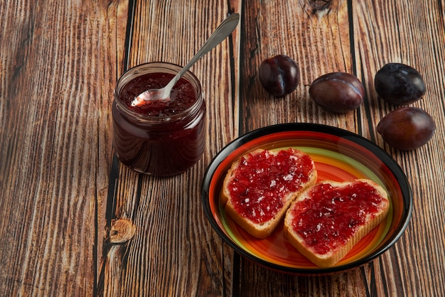 Plum confiture in the glass jar and on the toast.