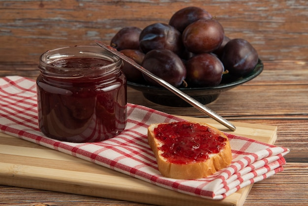 Plum confiture in a glass jar with toast breads and fruits on a kitchen towel.