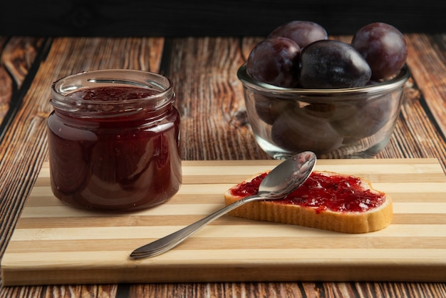 Plum confiture in a glass jar with toast breads and fruits.
