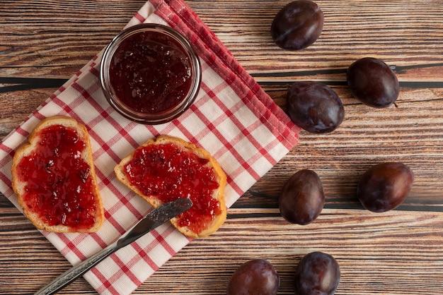 Confettura di prugne nel barattolo con toast e frutta intorno.