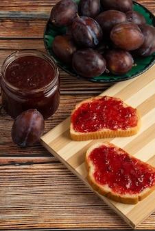 Confettura di prugne su pane tostato e frutta.