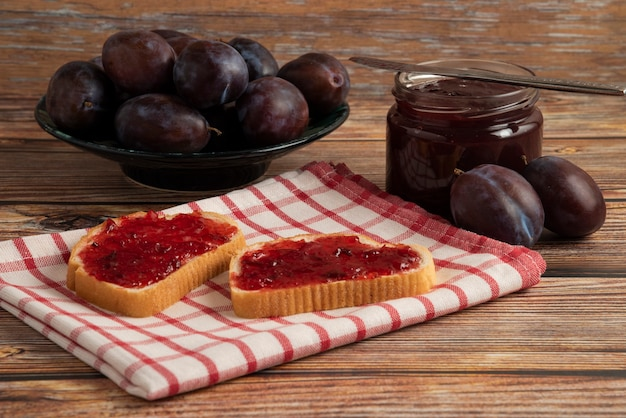 Plum confiture on the toast on the checked towel.