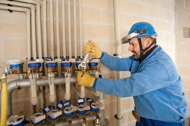 Сантехник регулирует водопроводные краны