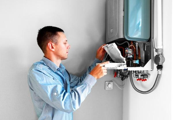 Водопроводчик пытается решить проблему с отопительным оборудованием для дома