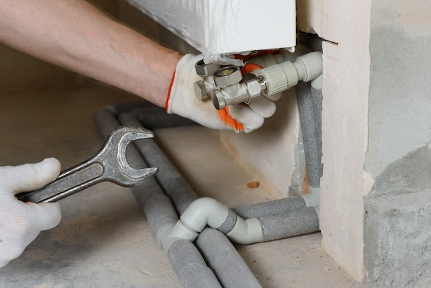 A plumber attaching the pipes of the heating system to the radiator