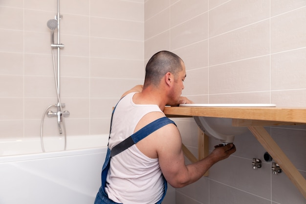 Plumber in blue denim overalls fixing sink in bathroom with tile wall