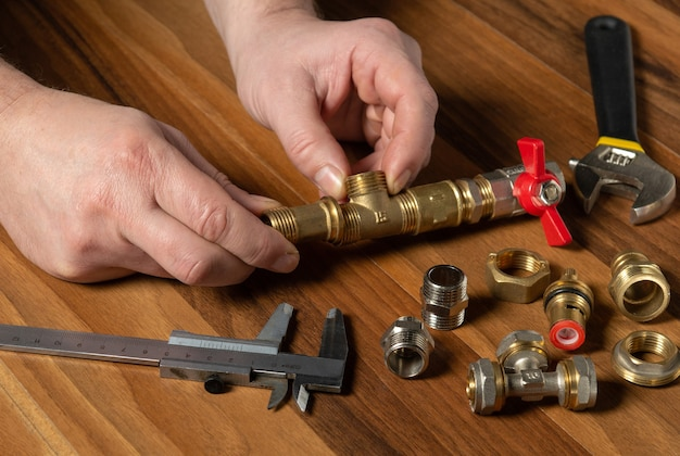 배관공은 장비를 수리하는 동안 황동 피팅을 연결합니다.