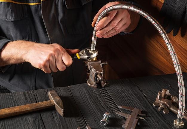 配管工は、機器の修理中に高圧ホースを接続します