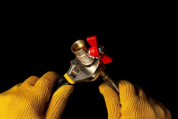 배관공은 조절 가능한 렌치를 사용하여 호스를 볼 밸브에 연결합니다.