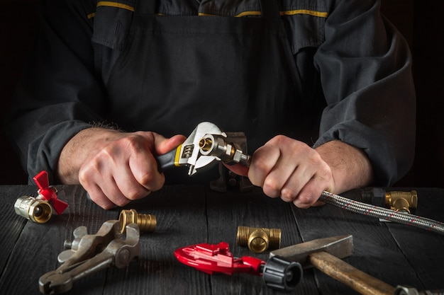 배관공은 조정 가능한 렌치를 사용하여 황동 피팅을 수도꼭지에 연결합니다. 작업장의 클로즈업은 작업장에서 일하는 동안 손입니다