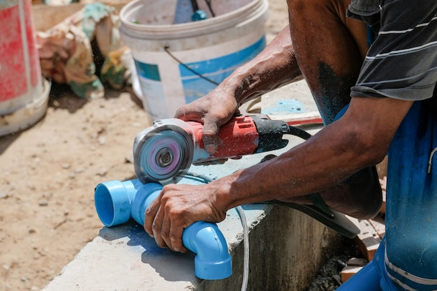 Plumber cutting PVC pipe with grinder in construction site. & Pvc Pipe Vectors Photos and PSD files | Free Download