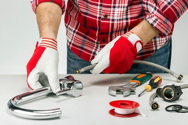 配管工の蛇口の設置またはキッチンの給水栓の修理。配管サービスのコンセプト。