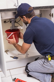 Plumber fixing under the sink